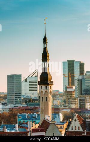 Tallinn, Estonia. Tower Of Tallinn Town Hall On Background Of Modern Architecture. Oldest Town Hall In Baltic Region - Stock Photo