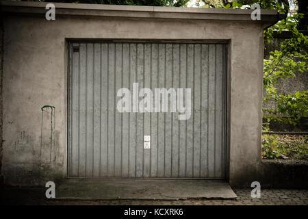Old garage with metal door - Stock Photo