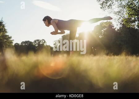 Mature woman in park, balancing on one leg, in yoga position, low angle view - Stock Photo