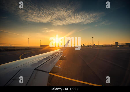 View of the airport and airplane wing from the Inside - Stock Photo