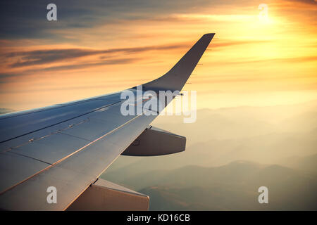 View of the clouds and airplane wing from the Inside - Stock Photo