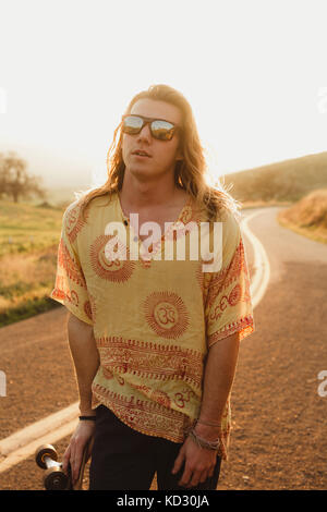 Portrait of long haired young male skateboarder on rural road, Exeter, California, USA - Stock Photo