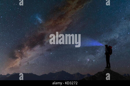 Silhouette of climber on mountain peak looking away at starry night sky, Chamonix, Mont Blanc, Rhone Alpes, France, - Stock Photo