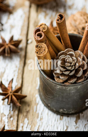 Christmas Baking Ingredients Cinnamon Sticks Scattered Anise Star Walnuts Pine Cone in Vintage Jug on Wood Background. - Stock Photo
