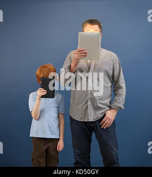 adult and child looking at tablets - Stock Photo