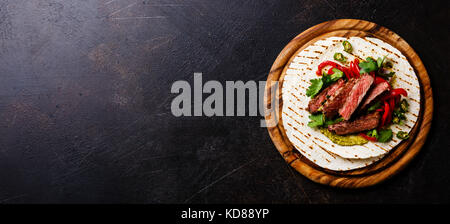 Grilled Beef steak Fajitas taco tortillas with green salsa and bell pepper on dark background copy space - Stock Photo