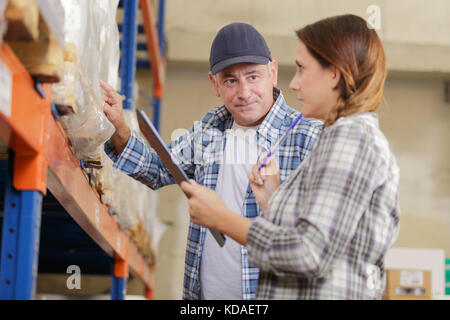 co-workers in a warehouse checking inventory levels of goods - Stock Photo