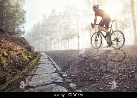 Cyclist on road in a foggy forest - Stock Photo
