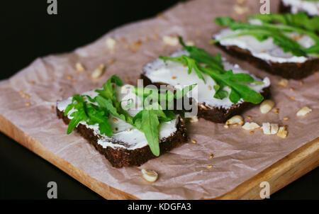 Vegetarian sandwiches on grain bread, soft cheese, walnuts and arugula - Stock Photo