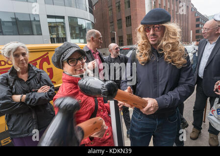 London, UK. 14th October 2017. Class War play with inflatable hammers as the prepare to protest peacefully outside - Stock Photo
