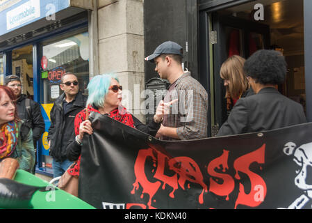 London, UK. 14th October 2017. Class War asks two people leaving the so-called 'museum' in Cable St  if they enjoyed - Stock Photo