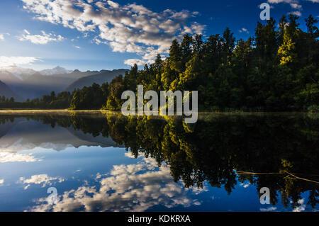 Lake Matheson, Fox Glacier, West Coast • New Zealand   Reflection of Aoraki (Mt. Cook)  and Rarakiora (Mt. Tasman) - Stock Photo