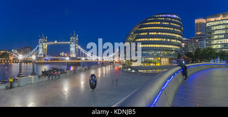 London - The panorama of the Tower bridge, promenade with the the modern Town Hall building at dusk. - Stock Photo