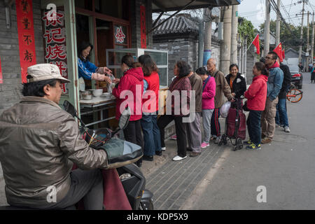 Residents line up to buy cakes in a Hutong in Beijing, China. - Stock Photo