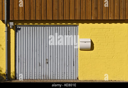 Yellow brick wall with garage door, mail box, downspout and brown wooden paneling on the second floor - Stock Photo