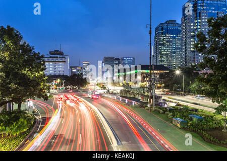 traffic light trails along Jakarta main avenue in the business district, Jalan Thamrin, at night in Indonesia capital - Stock Photo