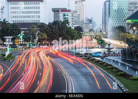 Traffic, captured with blurred motion, rushes along the Thamrin avenue in the heart of Jakarta downtown district - Stock Photo