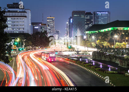 Traffic light trails along Jakarta main avenue in the business district at night in Indonesia capital city. The - Stock Photo