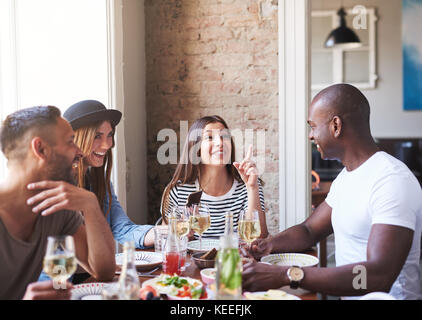 Diverse small group of four happy friends having wine and dinner together in restaurant with brick wall and bright - Stock Photo