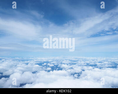 white clouds and blue sky as seen through window of an aircraft. panorama cloudscape - Stock Photo