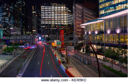 Skyscrapers in Paris business district La Defense. European night cityscape with dynamic street traffic, car lights - Stock Photo