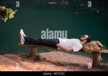 Man Relaxing Outside. Wearing a white T shirt, dark pants, sunglasses, a young guy is lying down on wooden bench - Stock Photo