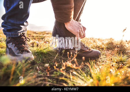 Active senior man on a walk in a beautiful autumn nature. Unrecognizable man tying his shoelaces. Close up. - Stock Photo