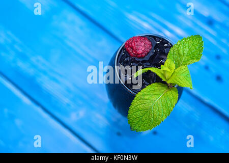 Dark restaurant cocktail with mint and raspberry - Stock Photo