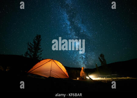 Tourist near his camp tent at night. - Stock Photo