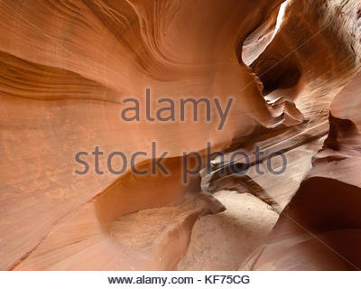 Slot canyon with smooth wavy orange walls reaching in from left - Stock Photo