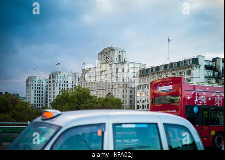Shell Mex House - London bus and taxi cross Waterloo Bridge in front of Shell Mex House in central London at dusk - Stock Photo