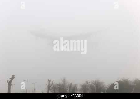 airliner on final-approach in fog at Heathrow - Stock Photo