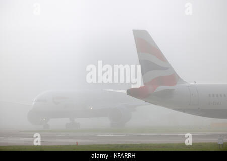 airliner taxiing at Heathrow in fog - Stock Photo