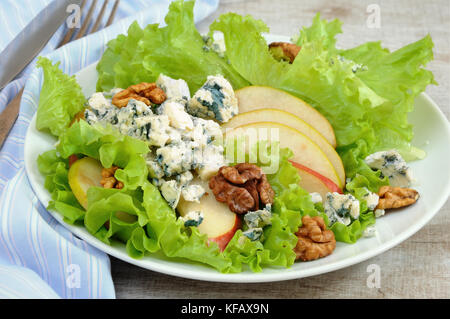 A light lettuce salad with pear slices, gorgonzola pieces and walnut seasoned with olive oil - Stock Photo