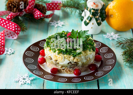 Homemade snacks on a festive Christmas table. Fish salad with mushrooms, salmon, cranberries and cheese. - Stock Photo