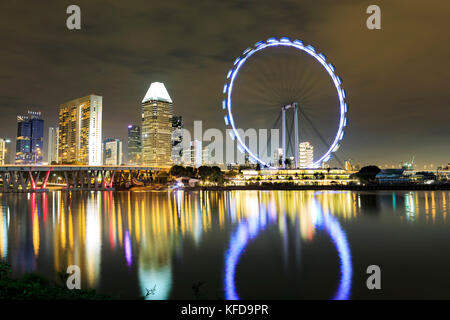 Marina Bay view with Singapur Flyer and skyline of Singapore town by night - Stock Photo