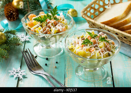 Home holiday snacks Christmas table. Salad with salmon, potatoes and pickled cucumber. - Stock Photo