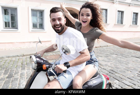Portrait of happy young couple on scooter enjoying road trip - Stock Photo