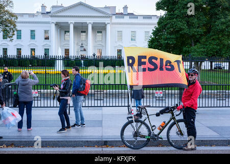 Protester standing in front of the White House holding a Resist banner/flag, protesting against president Trump, - Stock Photo