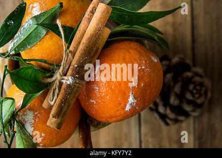 Vibrant Orange Tangerines on Branches Green Leaves Cinnamon Sticks tied with Twine Pine Cone Wood Background. Christmas - Stock Photo