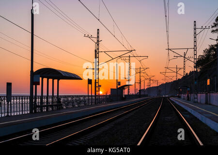 The platform of the railway station and the railroad going into the distance at sunset, Sochi, Russia - Stock Photo
