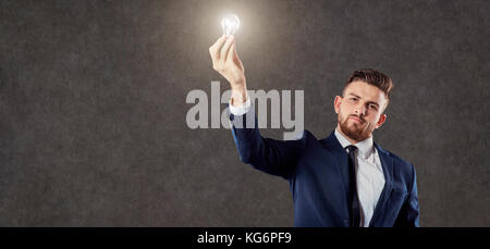 Businessman with luminous light bulb in hand. - Stock Photo