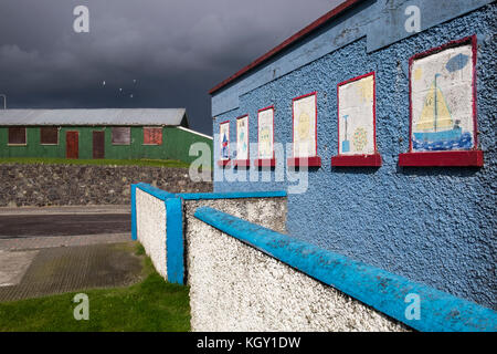 Naive painted windows on a pebble dash building and corrugated tin hut in Laytown, County Meath, Ireland - Stock Photo