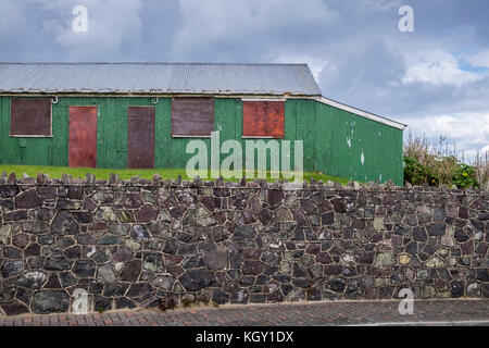 Corrugated iron shed, tin hut, derelict, boarded up in Laytown, County Meath, Ireland - Stock Photo