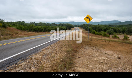Low Angle Shot of Country Road With Yellow TRaffic Sign in the Foreground - Stock Photo