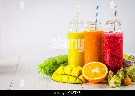Multicolored smoothies in bottles of mango, orange, banana, celery, berries, on a wooden table - Stock Photo