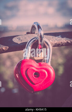 Symbol of love. Vintage card with red heart background. Metal lock on bridge of lovers. - Stock Photo