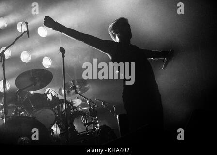 Rock Concert where the lead singer or frontman is in the position of the crucifix also with the stage lights behind - Stock Photo