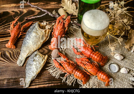 Beer with foam in glass and dried salted fish and with boiled red crayfish on canvas,lying on dark wood boards - Stock Photo