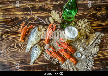 Beer with foam in a glass and a bottle of beer with a snack of boiled crawfish and dried salted fish on dark wood - Stock Photo